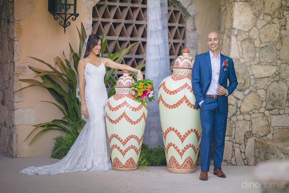 This lovely couple is posing infront of big decorative pots after the completion of wedding ceremonies- Nikki and David