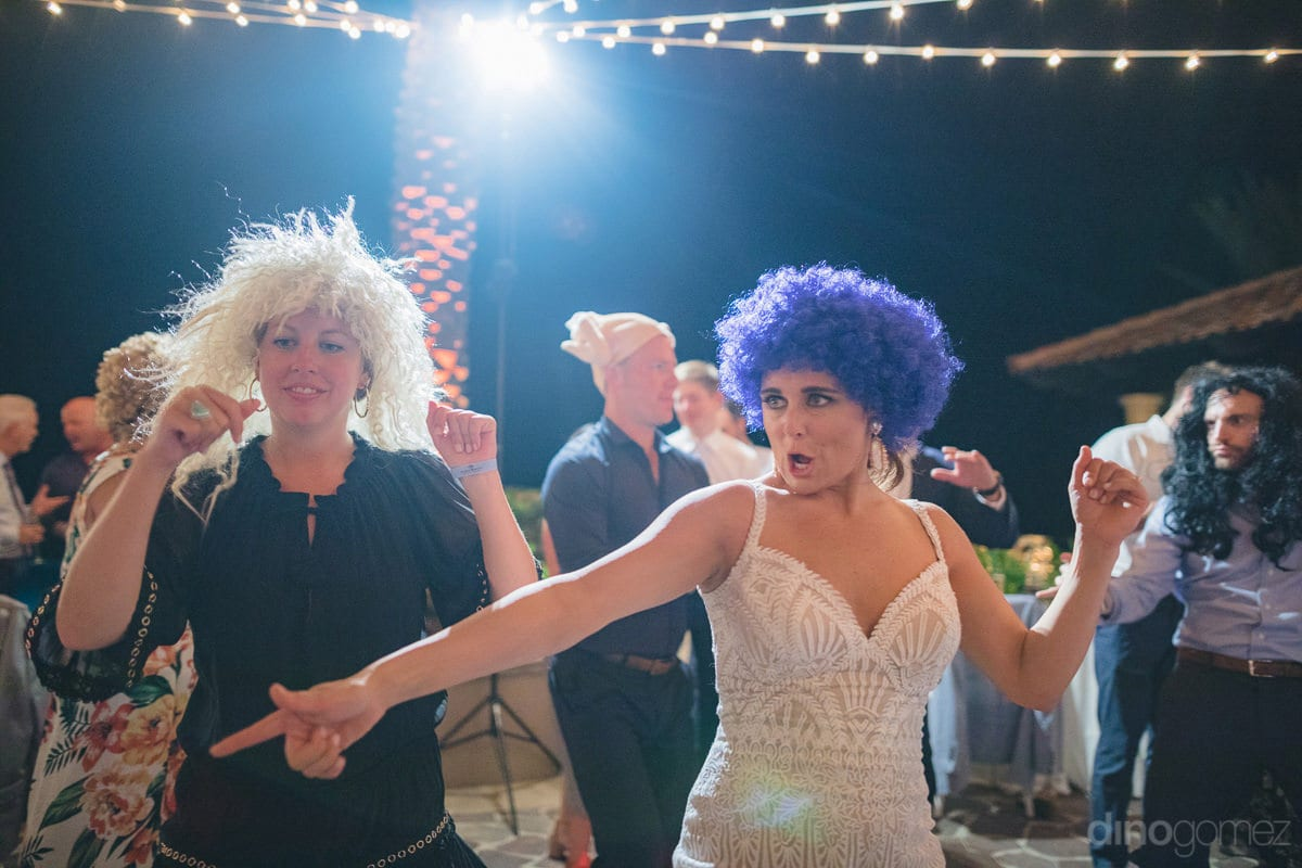 Gorgeous bride and her friends can be seen dancing like crazy with head wigs at the reception party- Kathleen & Kevin	The bride and other wedding guests can be seen wearing colored head wigs and grooving on the dance beats at the evening reception party-