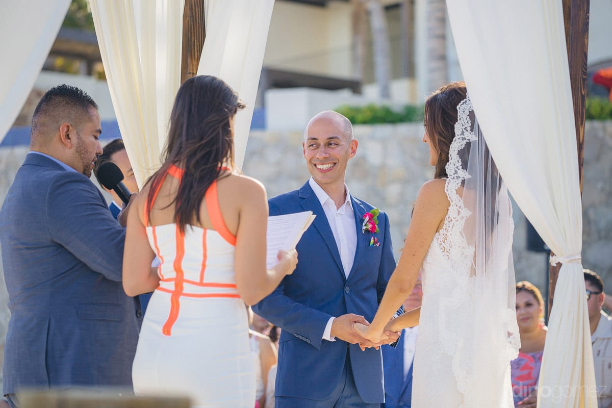 Handsome groom is smiling broadly while looking at the person reading their wedding vows- Nikki and David
