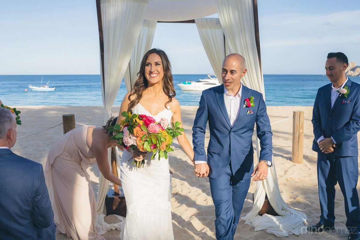 Gorgeous couple is walking hand in hand at the beachside on their wedding day with big smiles on their face- Nikki and David