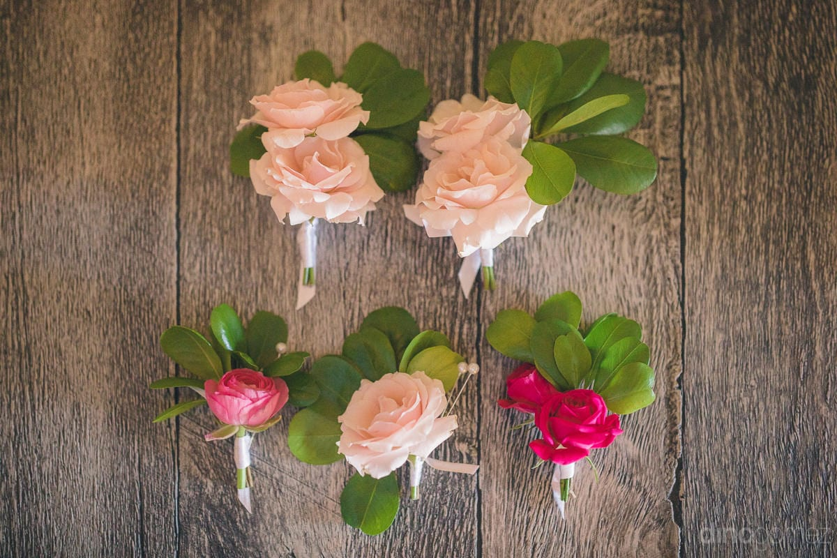 Cute roses tied with their leaves are placed on a wooden surface- Nikki and David