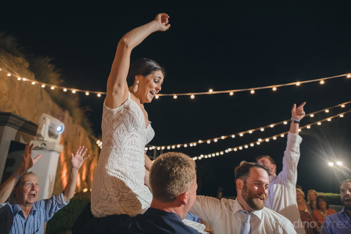 The new bride is sitting on shoulders of one of the gentleman at the reception party and enjoying the dance to the fullest- Kathleen & Kevin