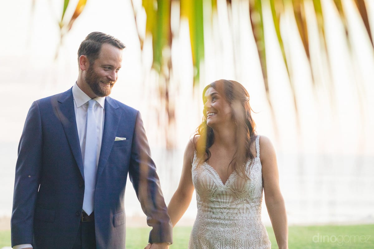 The lovely couple is walking while holding each others hands in the garden around the sea- Kathleen & Kevin