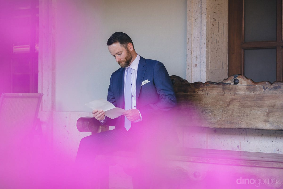 The groom can be seen giving a read to a piece of paper while sitting at an open place in the lawn- Kathleen & Kevin