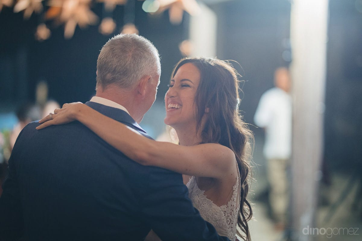The pretty bride is happily dancing with a gentleman at the evening reception party- Nikki and David	A gentleman is dancing with the beautiful bride at the evening reception party. The lovely bride is looking happy while dancing with the gentleman- destin