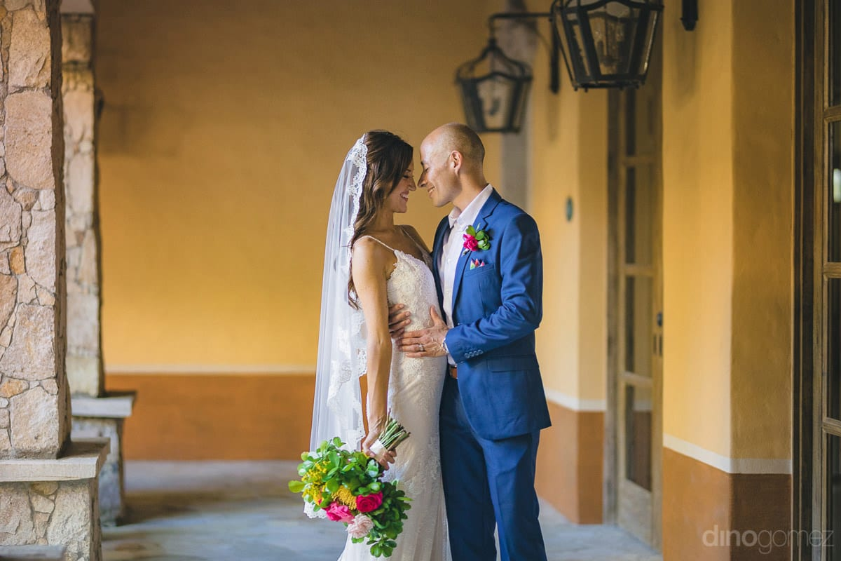 The bride and groom are happily posing for the camera hugging each other while standing in a corridor- Nikki and David