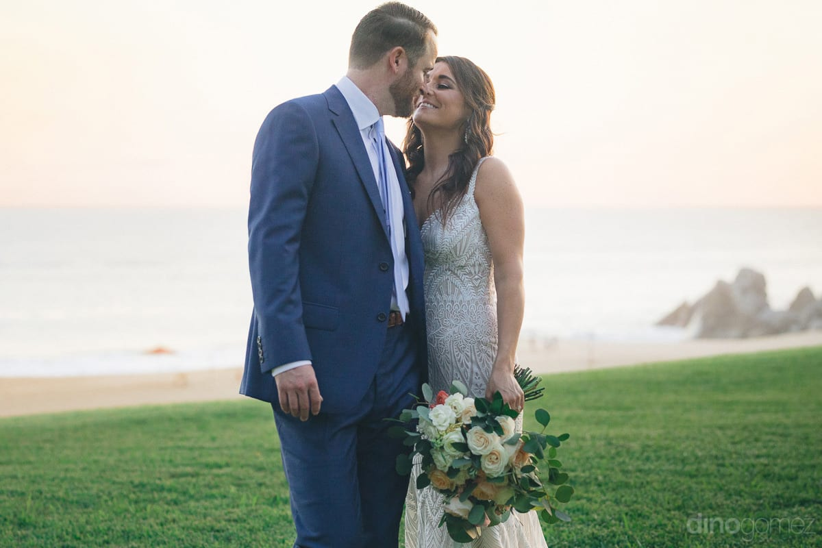The couple is giving a romantic pose for the camera while standing next to the sea- Kathleen & Kevin	Lovely bride and groom are standing very close to each other and are about to kiss each other under the beautiful orange sky and at the beachside- destina