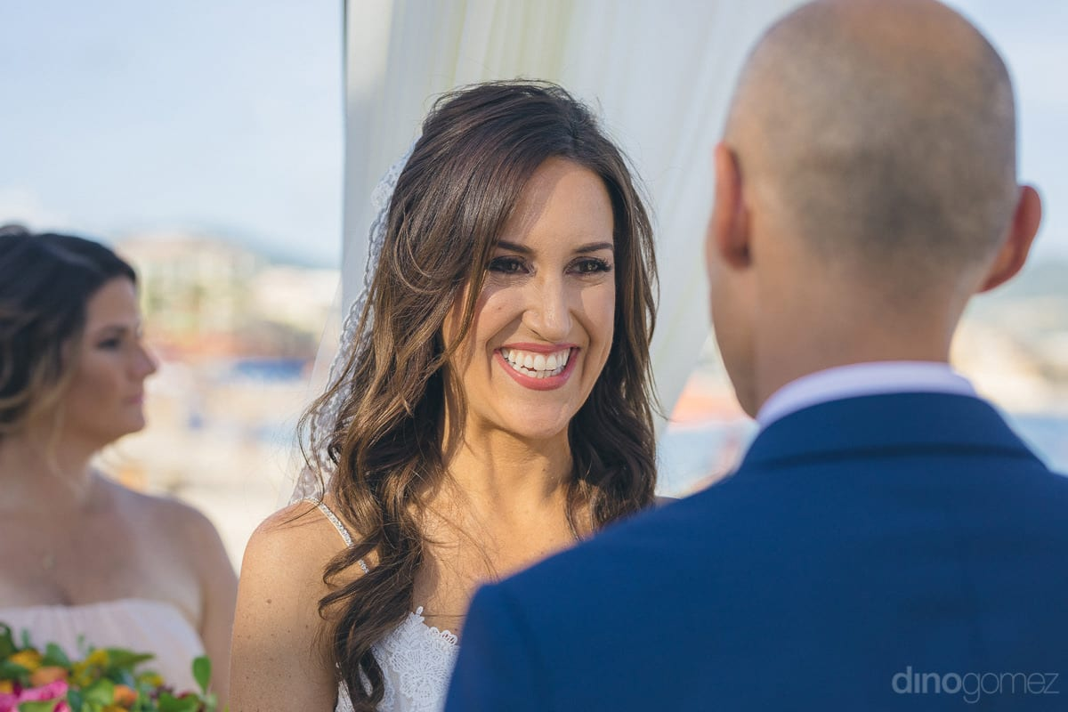 The gorgeous bride is smiling broadly while looking into the eyes of the handsome groom- Nikki and David