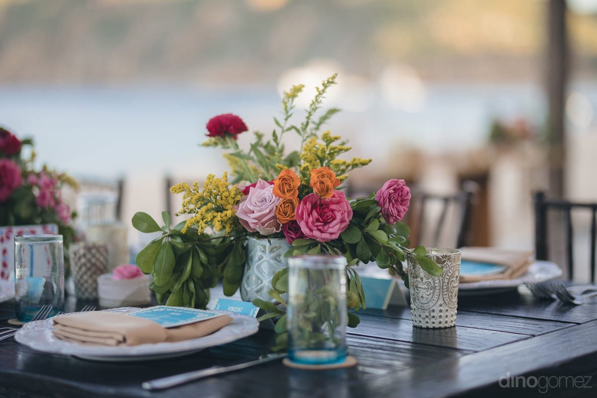 The dinning table of the wedding guests is beautifully decorated with colorful flowers and luxurious cutlery- Nikki and David
