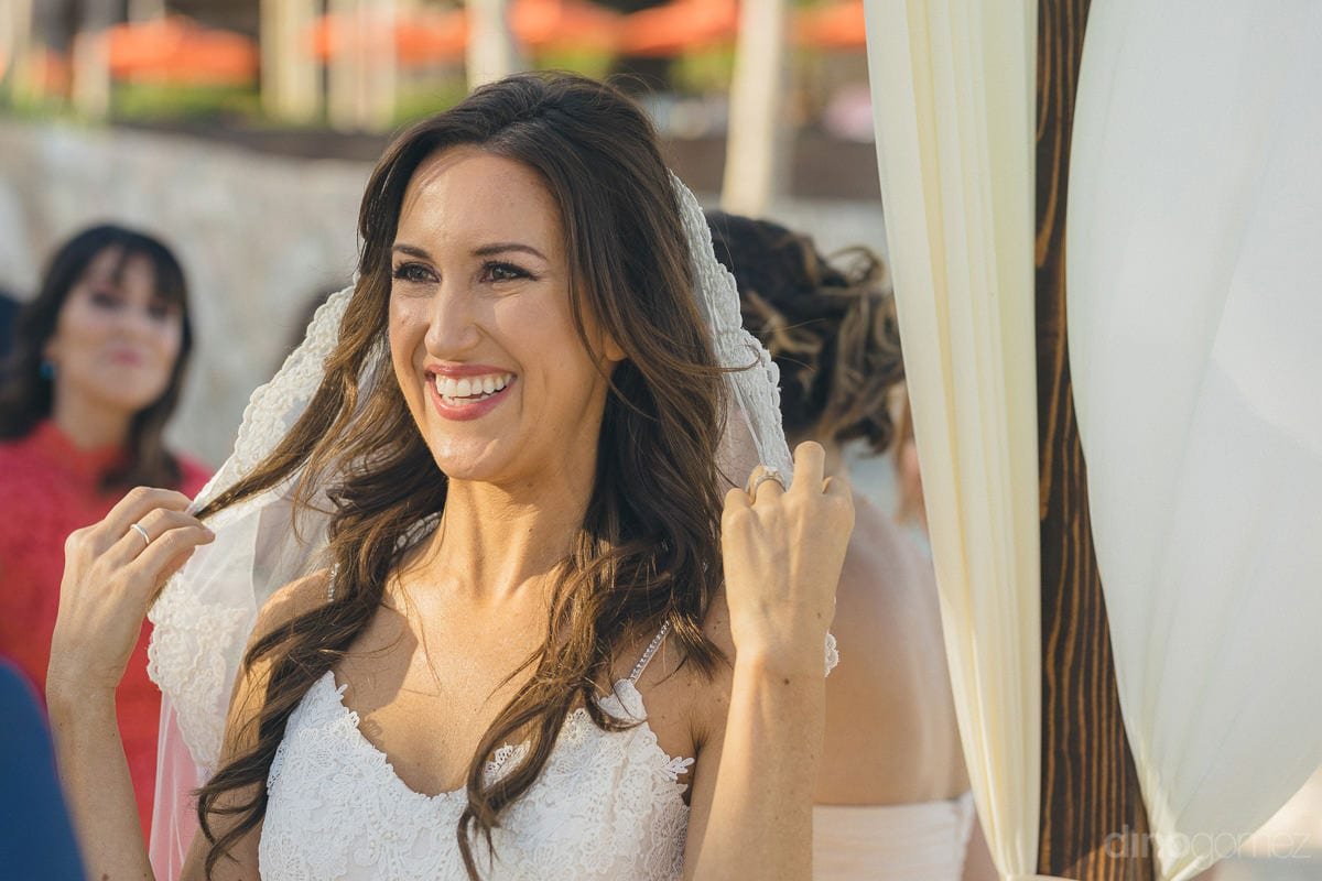 The gorgeous bride is setting her head veil and is smiling lovingly while doing so- Nikki and David