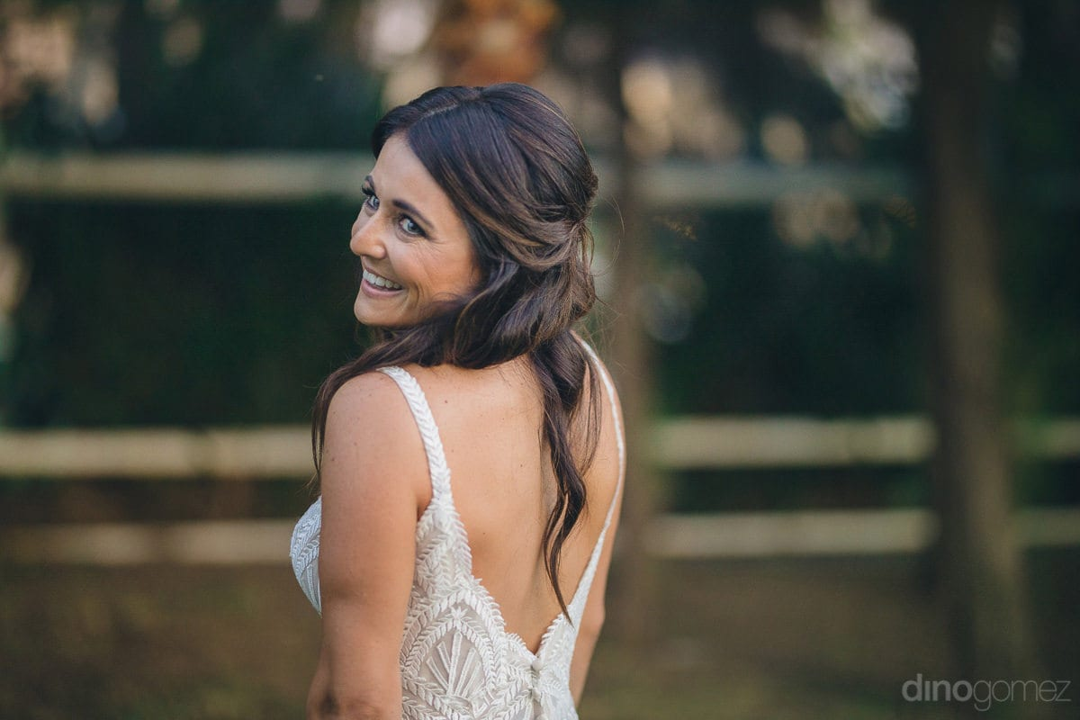Picture captures the lovely bride looking backwards and smiling brightly- Kathleen & Kevin	The gorgeous bride is standing in the lush green garden and is looking backwards wearing a pretty broad smile on her face- destination wedding of the gorgeous coupl