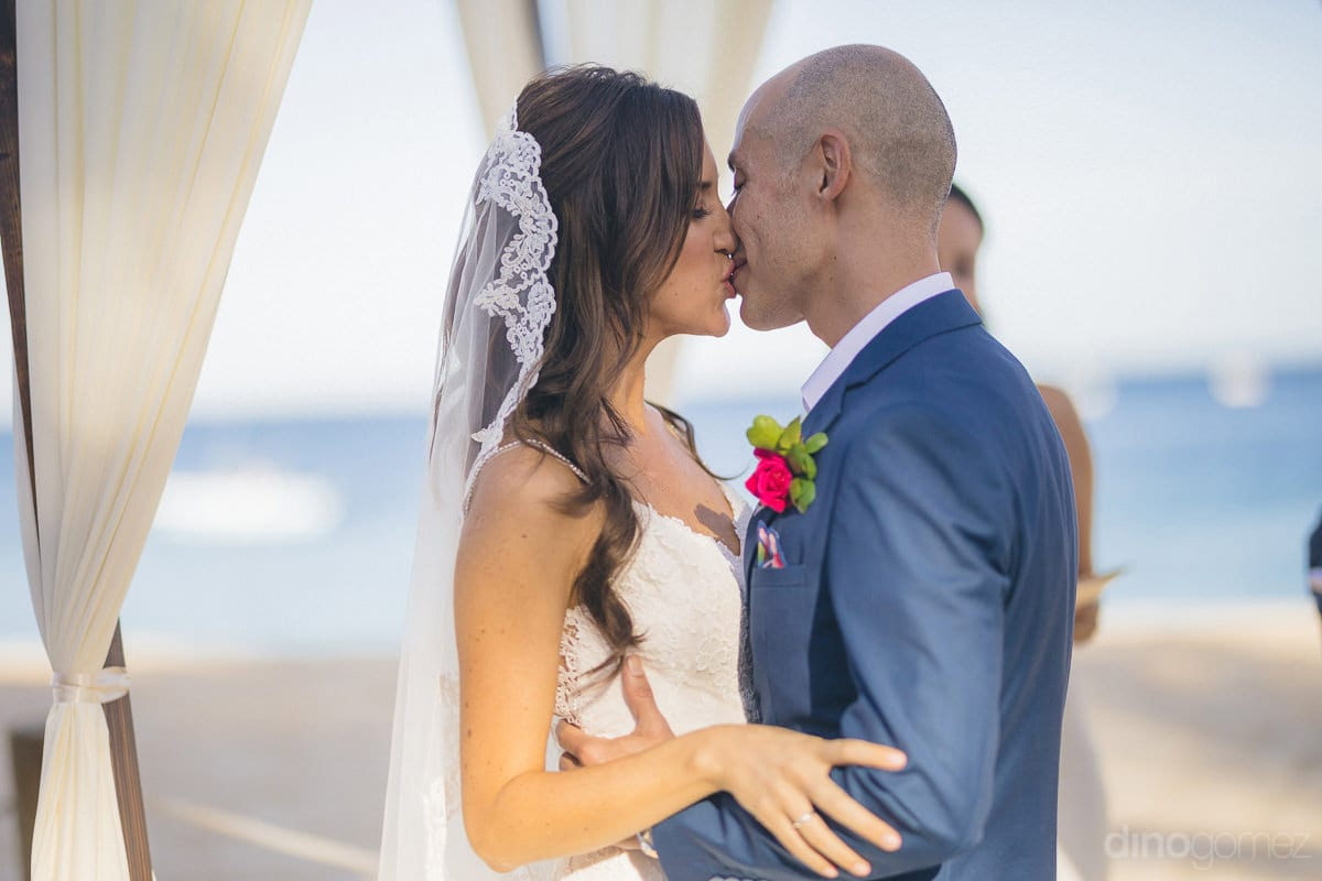 The lovely couple is kissing each other for the first time as husband and wife in the presence of wedding guests- Nikki and David