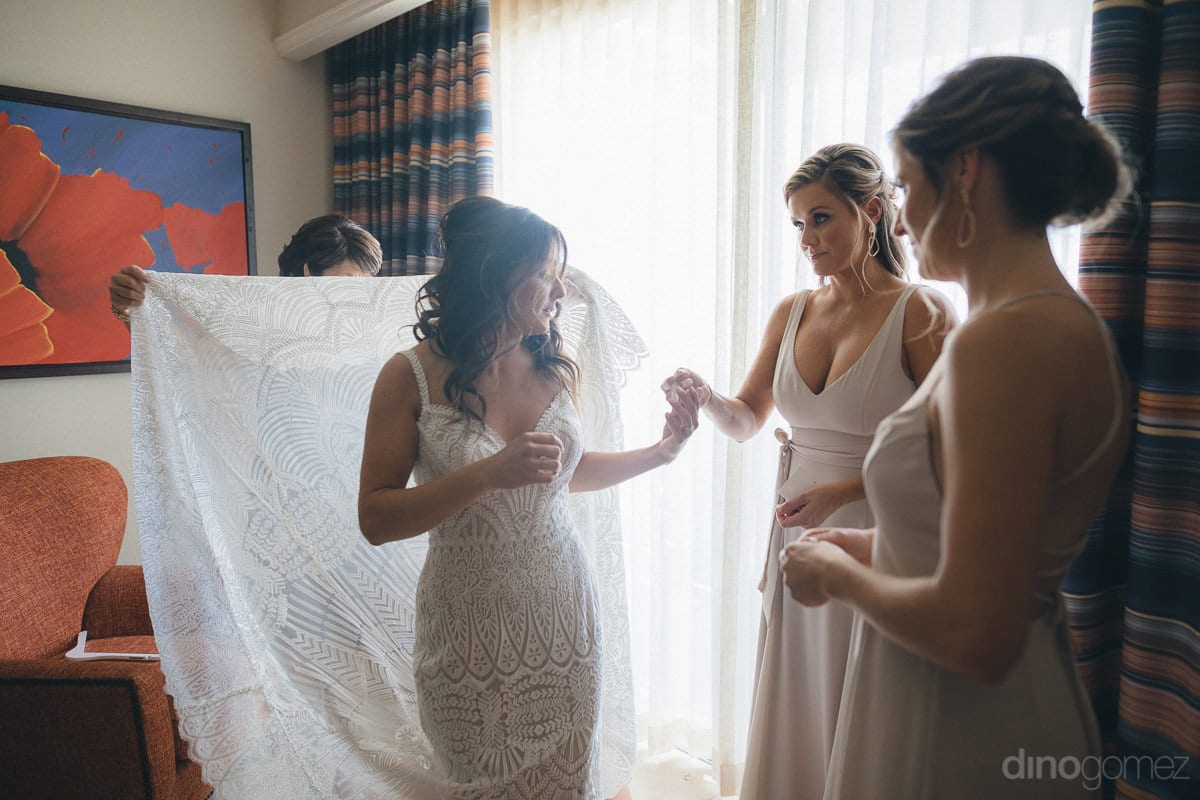 The picture beautifully captures a candid shot of the bride dressed in stunning white gown along with her bridemaids while getting ready for the wedding- Kathleen & Kevin