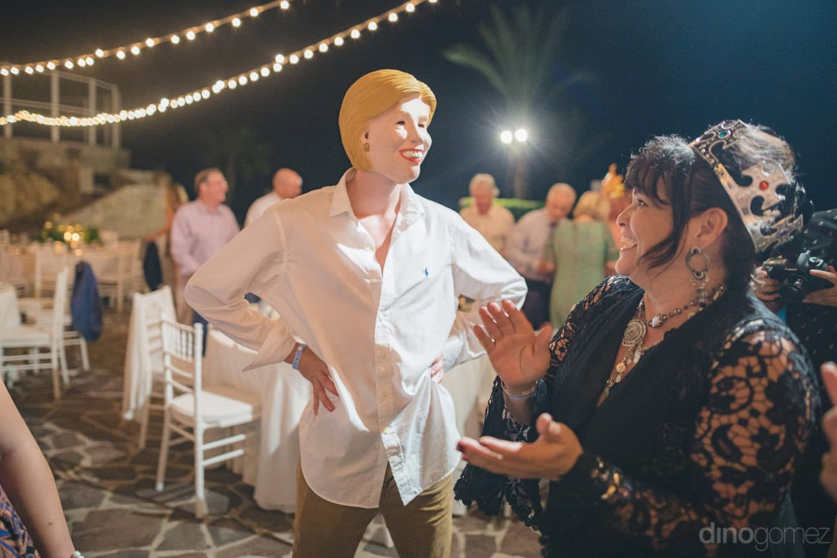 One of the gentleman is posing like a girl by wearing a face mask of a girl while other wedding guests are enjoying his performance completely at the reception party- Kathleen & Kevin