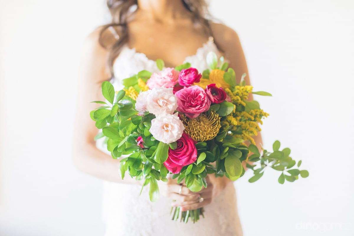 The gorgeous bride is showing her beautiful wedding bouquet holding in her hands- Nikki and David