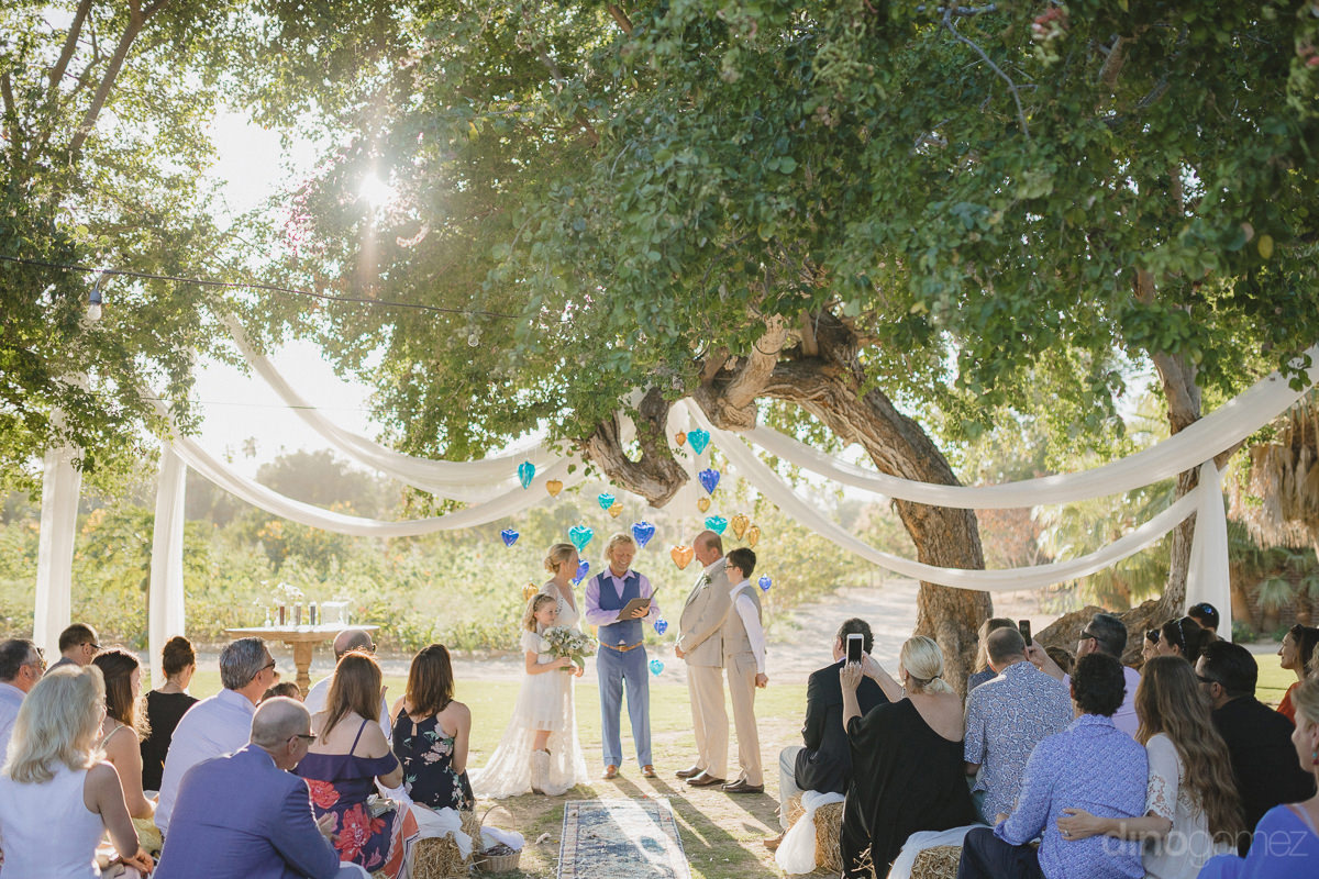 A Distant View Of The Gorgeous Couple Standing Under A Tree During The Vow Exchanging Ceremony Is Captured By The Destination Wedding Photographer- Lara & Darrell