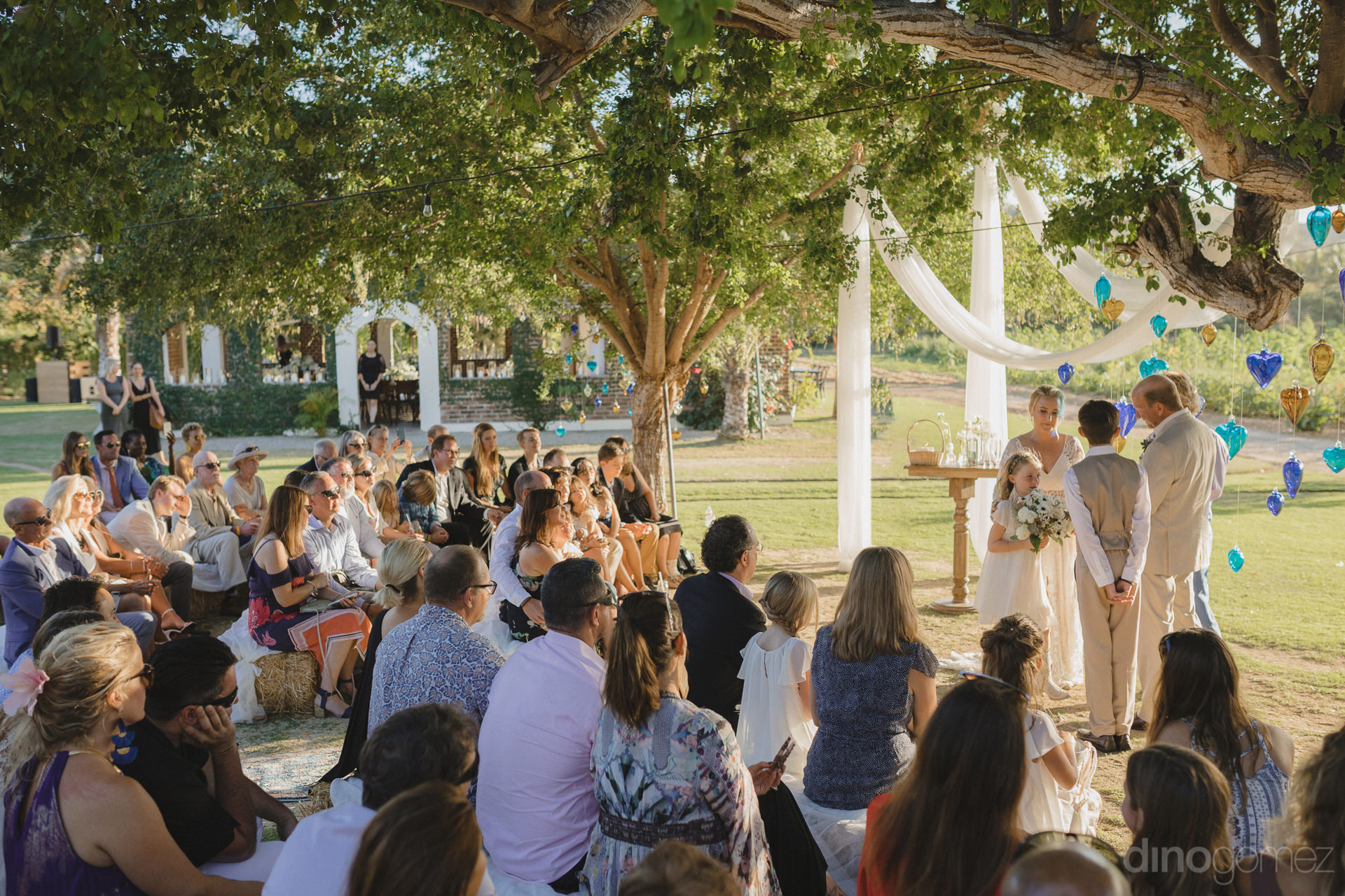 Picture taken by the destination wedding photographer captures beautifully the couple during their wedding ceremonies and guests sitting during the same- Lara & Darrell