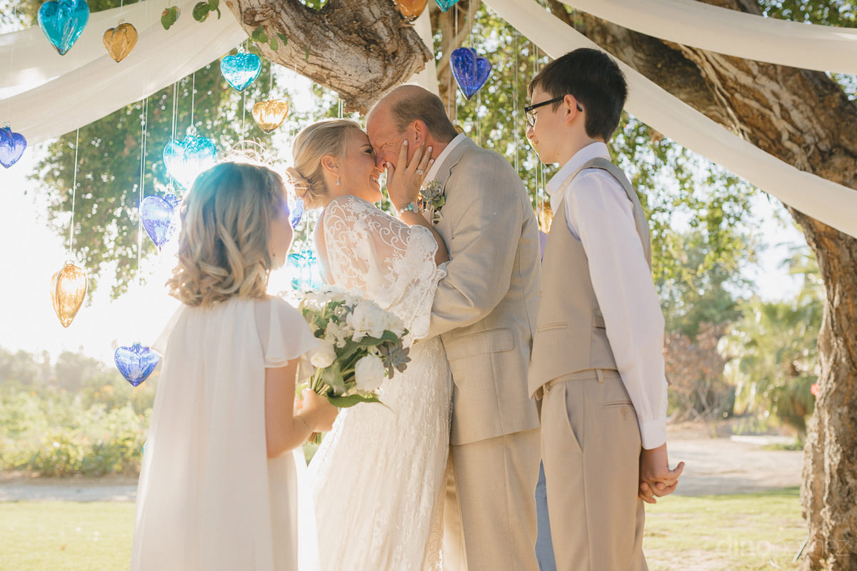 The Newly Married Couple Can Be Seen Happily Holding Each Others Face While Standing Under A Tree At The Oudoor Wedding Venue- Lara & Darrell