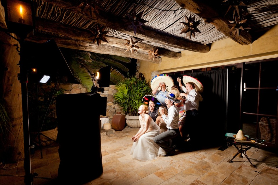 Destination wedding photo booth with the married couple and guests