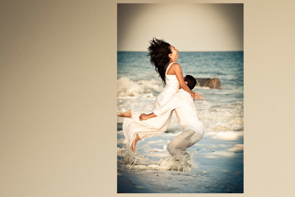 A shot of the bride jumping into her grooms arms on the beach by wedding photographer in Cabo Dino Gomez