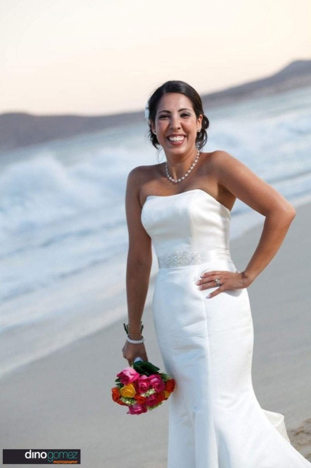 A stunning image of a smiling bride stood on the beach with her bouquet