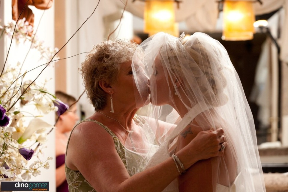 Bride gets a kiss on the lips from her mother on wedding day