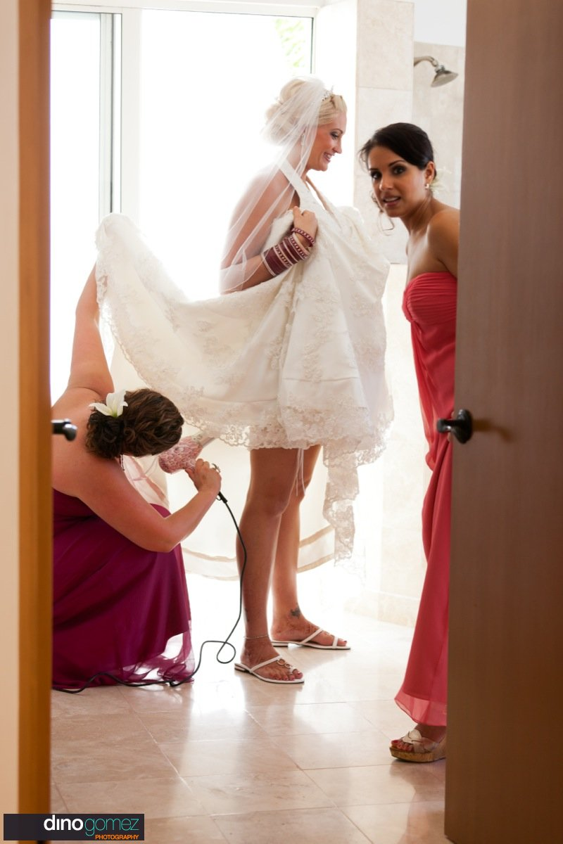 Bride gets her dress blow dried before the wedding