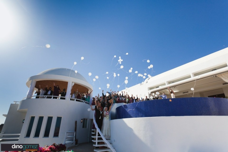 Newlyweds and guests release balloons after the wedding ceremony