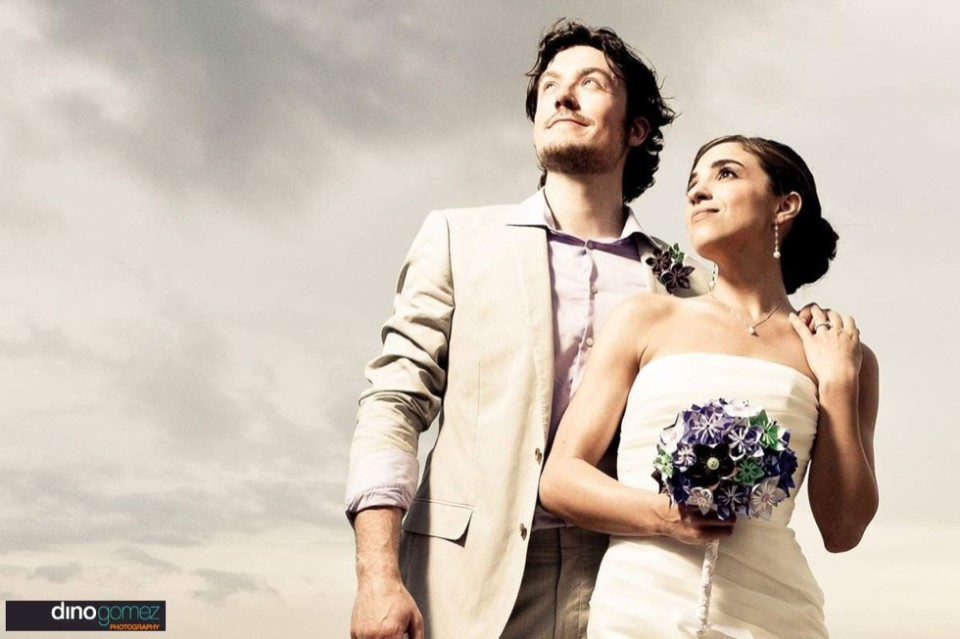 A beautiful photograph of a bride and groom looking towards the sky at their beach wedding