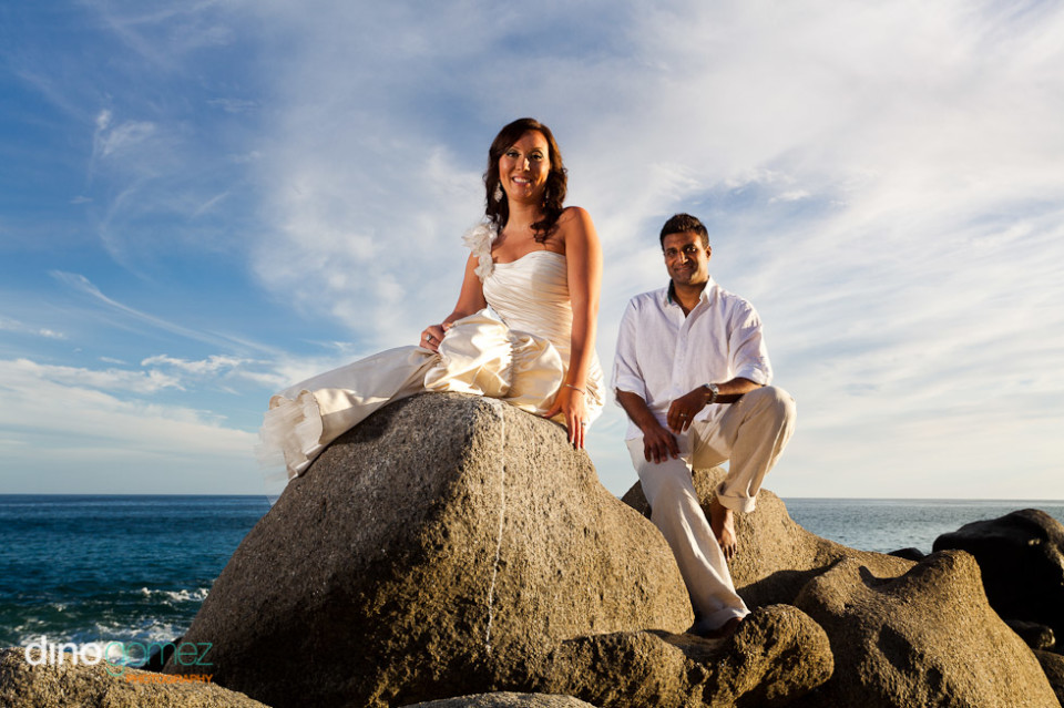 Bride in white wedding dress with the groom in white shirt sitting on rocks by the ocean