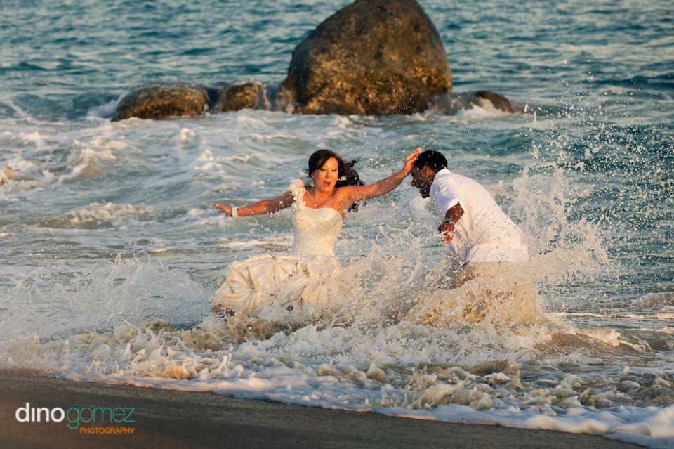 Happy Newlyweds Trashing The Wedding Dress In The Ocean