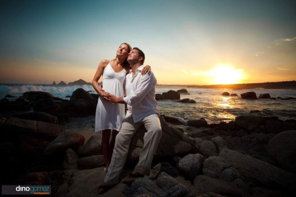 Romantic Sunset Beach Wedding Shot Of The Bride And Groom On The Rocks