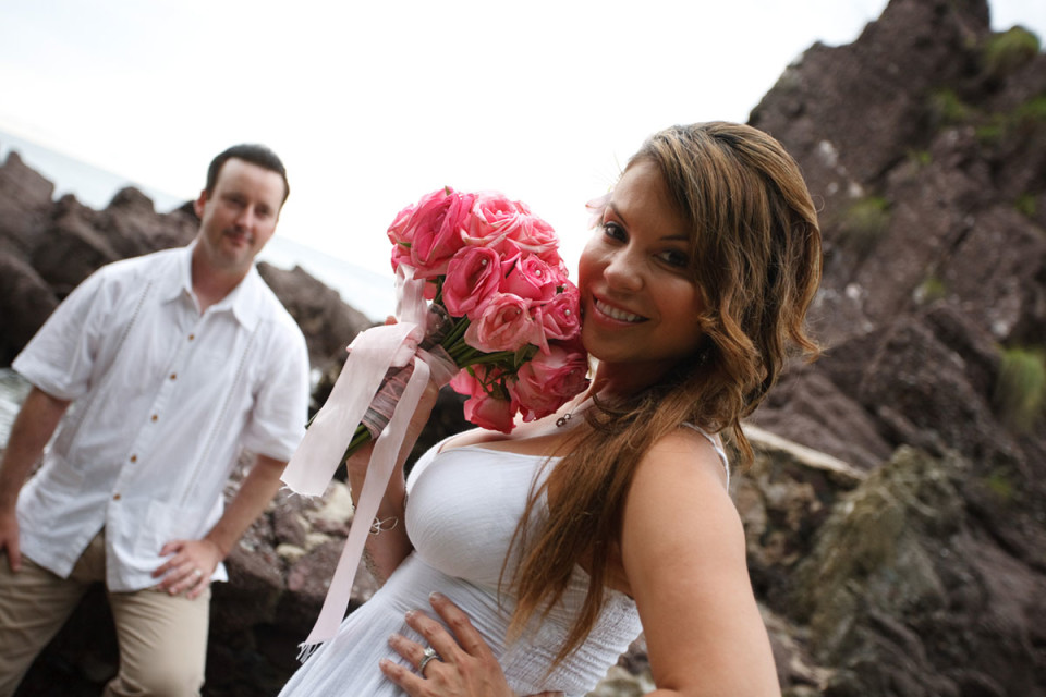 The happy bride holding a bouquet near her face in Mexico