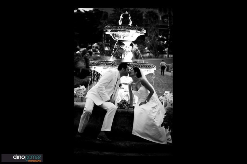 Bride and groom kissing in front of a fountain in black and white on their wedding day