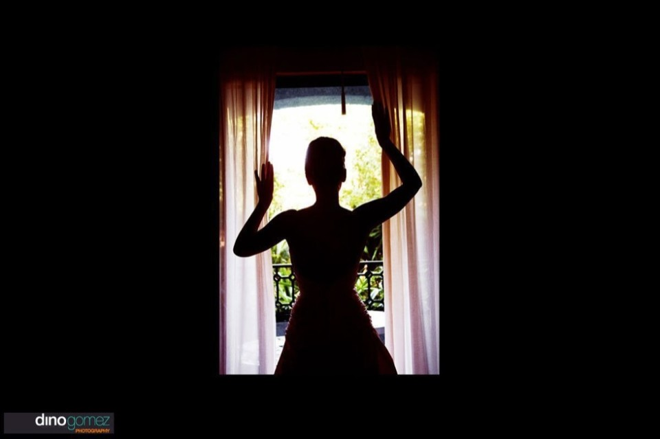Dramatic silhouette of the bride standing in front of the door way at her destination wedding