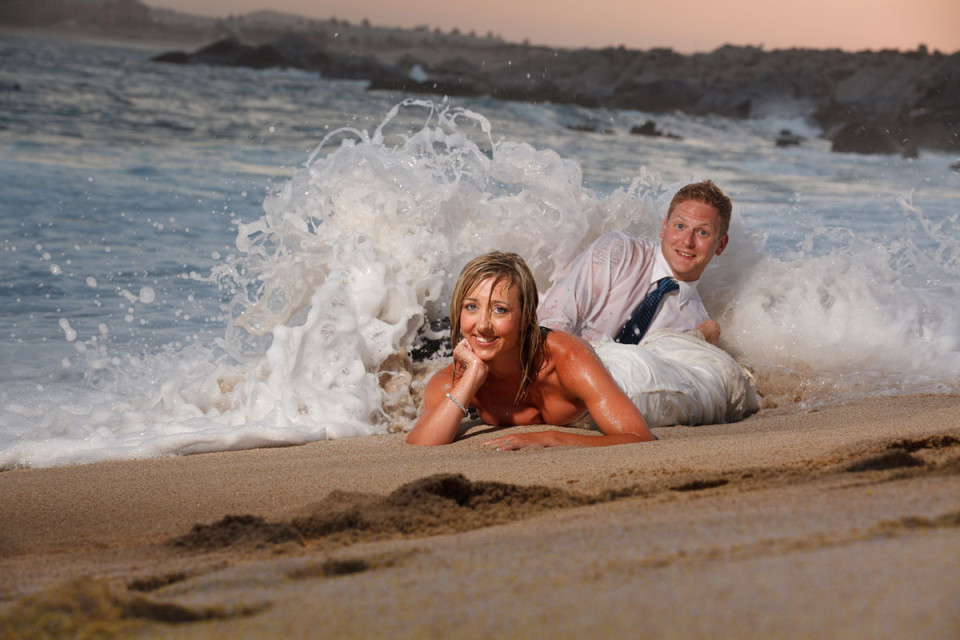 A gorgeous bride lying on her stomach with her groom on the shores in Mexico