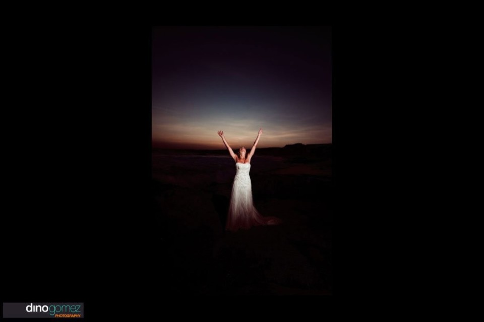 Bride in rustic sunset landscape with her hands in the air