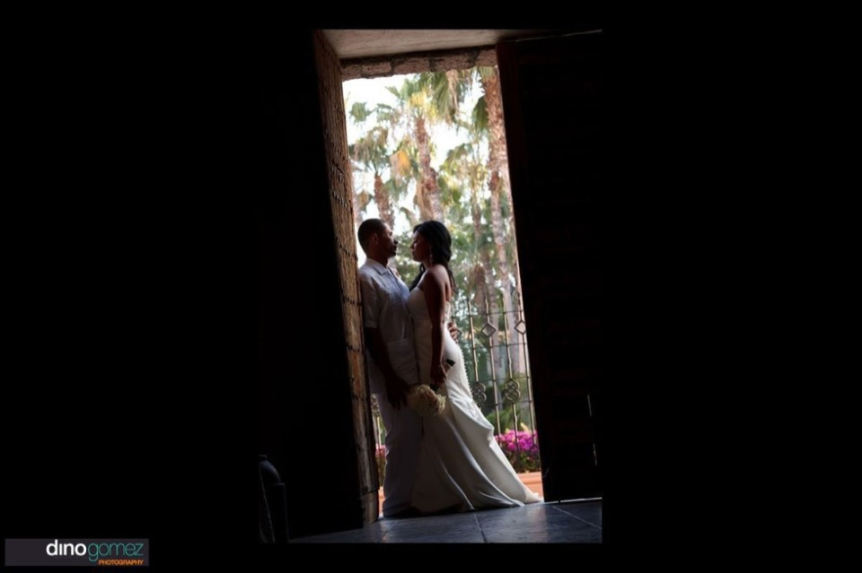 Bride and groom in a door way by a wedding photographer in Cabo Dino Gomez