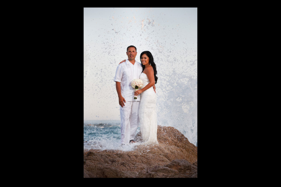 Wonderful wedding couple standing together on the beach with the waves crashing behind them