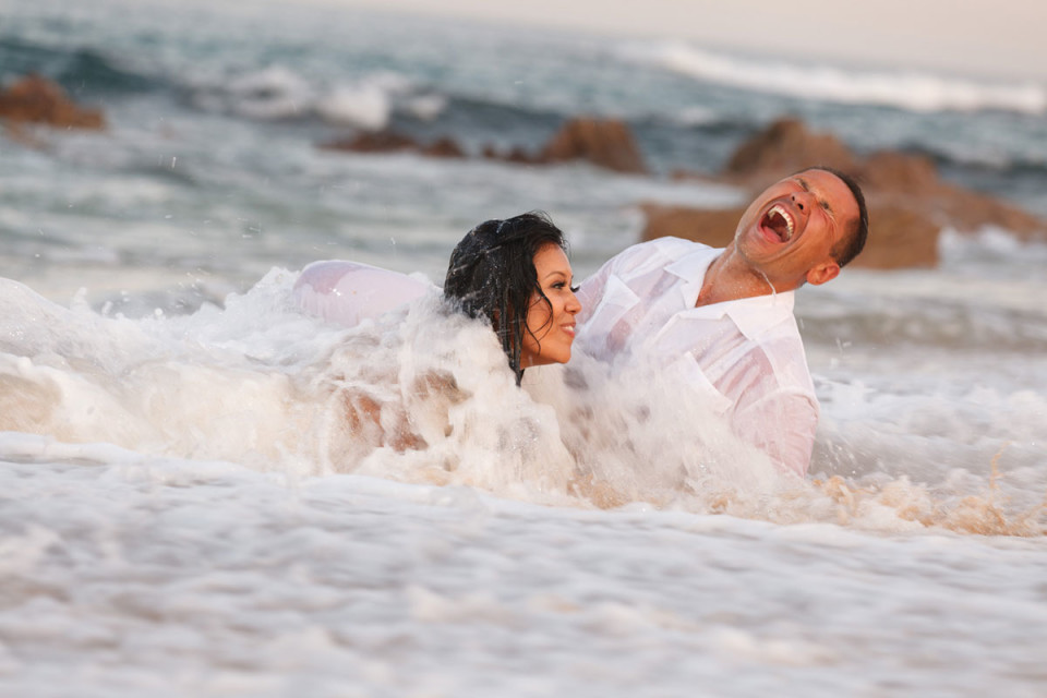 Newlyweds trashing their wedding attire in the ocean