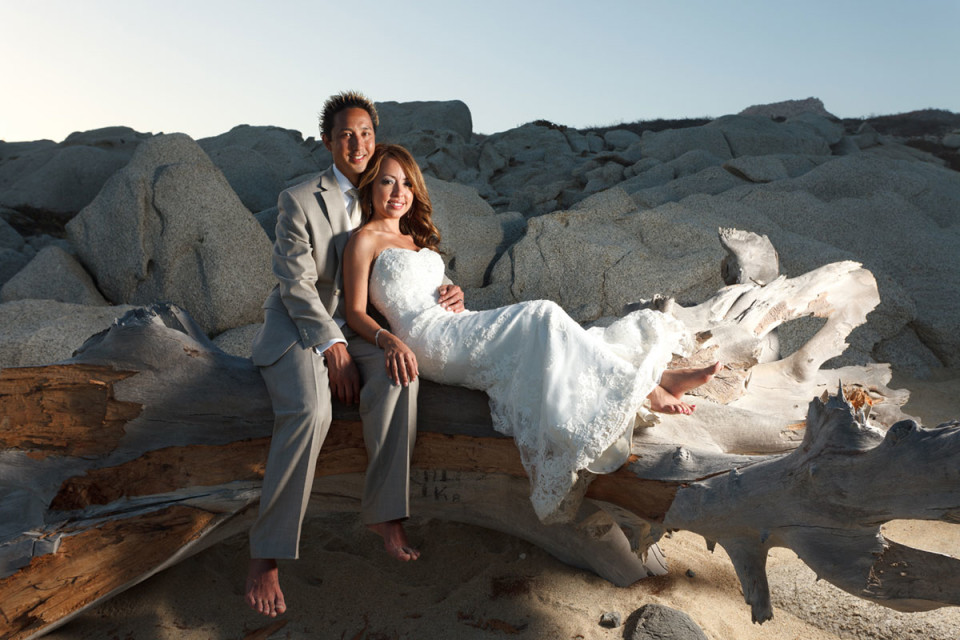 A snapshot of a bare footed wedding couple relaxing on a beach log in Mexico