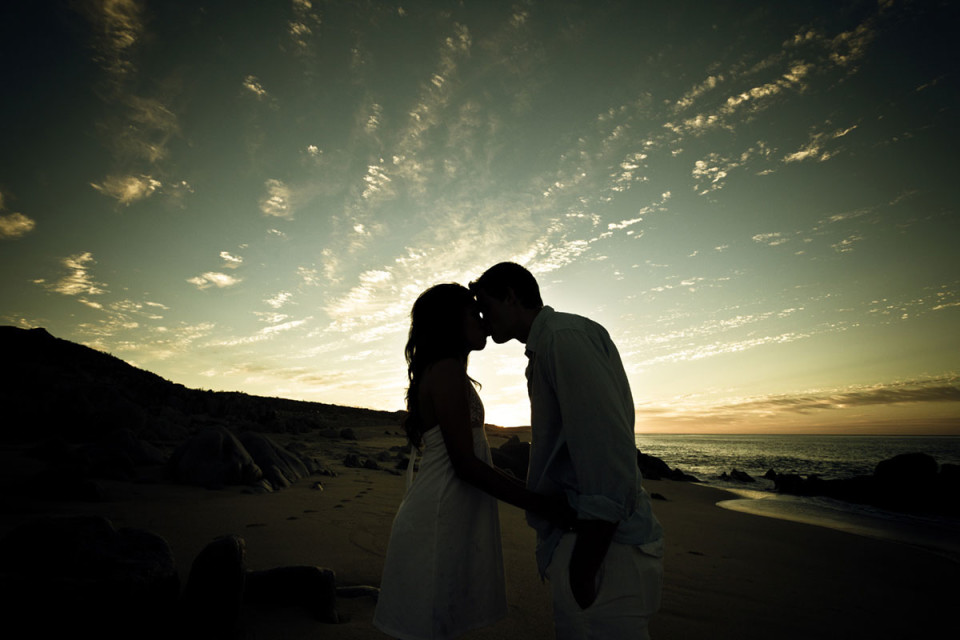 Beautiful kiss between the bride and groom on the beach at dusk in Mexico