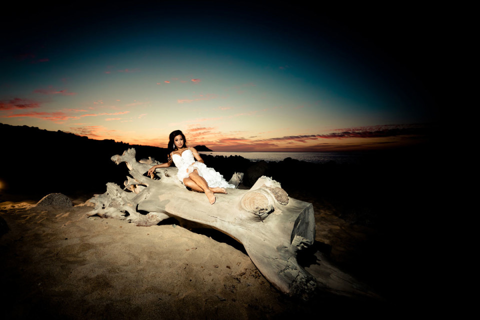 Beautiful bride lying on a log in the night on the beach