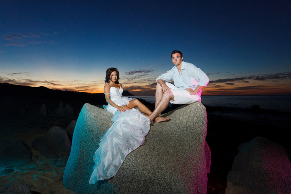 A bride and groom sitting on a beach boulder in Mexico
