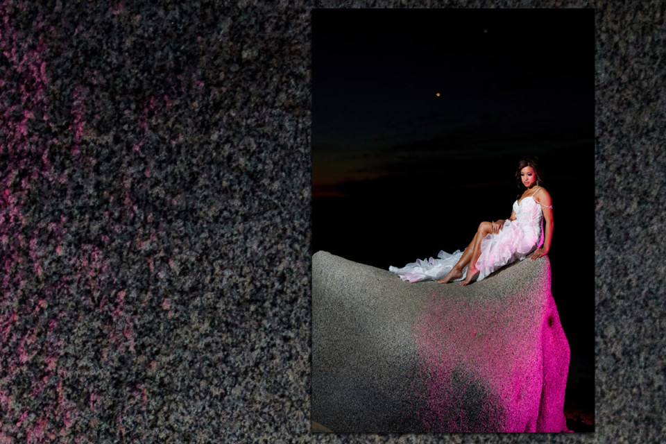 A sitting bride looking down on the beach in Mexico in the night