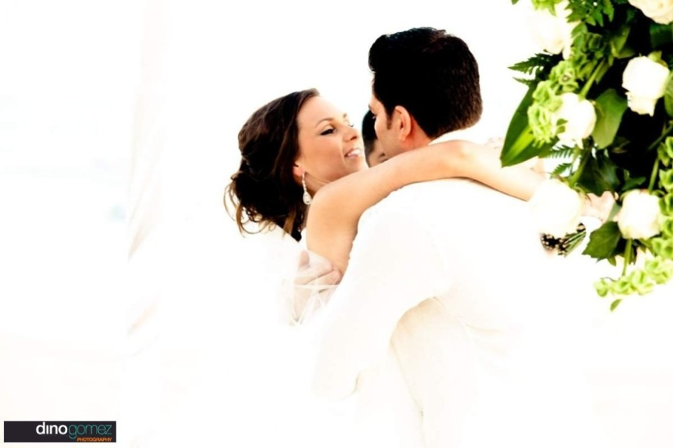 A newlywed couple embrace as they are married at their destination wedding