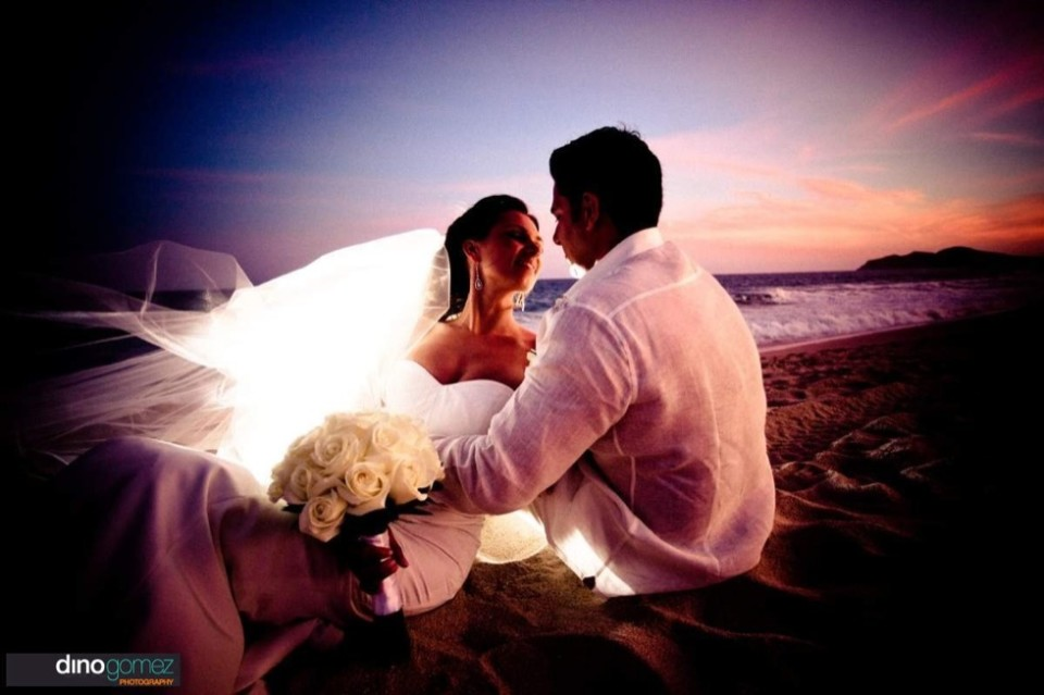 Two newlyweds share a romantic embrace on a beach at sunset.