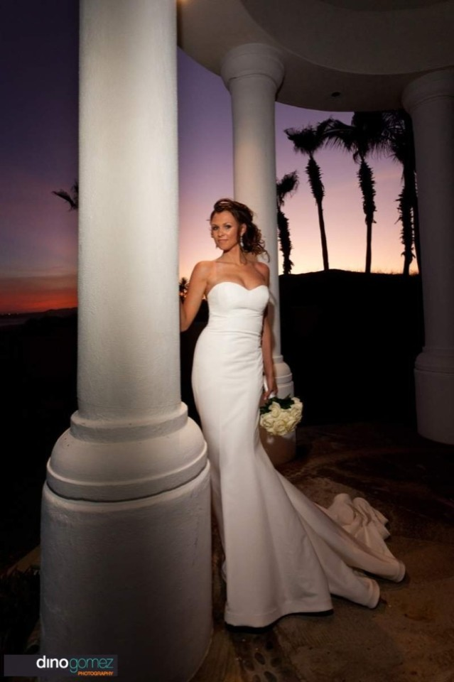 A stunning bride poses with a beautiful column at sunset in a photo taken by Dino Gomez