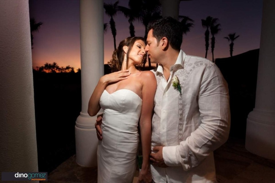 Husband and wife stare lovingly into each others eyes at sunset. Taken by destination photograper Dino Gomez
