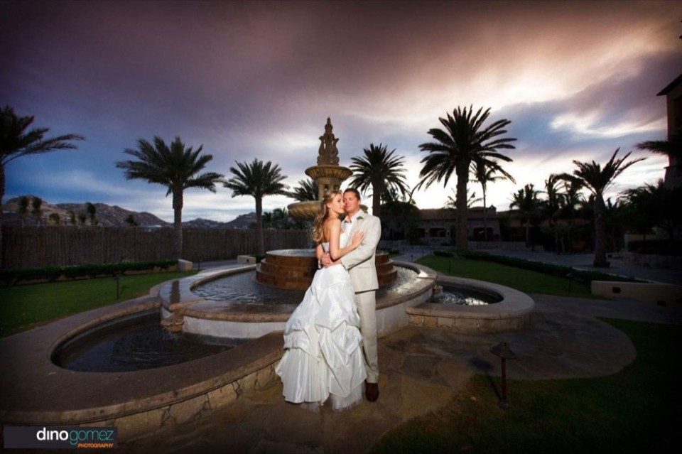 Wedding photographer in Cabo Dino Gomez snaps the perfect shot of the bride and groom in front of a beautiful fountain